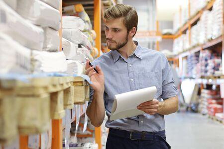 Hombre joven de compras o trabajando en un almacén de hardware de pie comprobando suministros en su tableta Foto de archivo