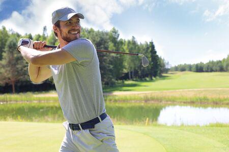 Golfer hits an fairway shot towards the club house
