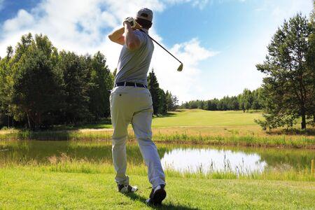 Volledige lengte van golfspeler die golf speelt op zonnige dag. Professionele mannelijke golfspeler die op golfbaan schiet Stockfoto