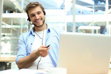 Souriant sympathique jeune opérateur de centre d'appels masculin