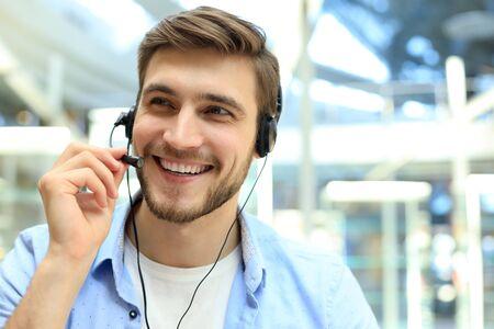 Souriant sympathique jeune opérateur de centre d'appels masculin Banque d'images