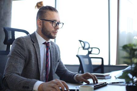Giovane premuroso in completo che lavora utilizzando il computer mentre è seduto in ufficio