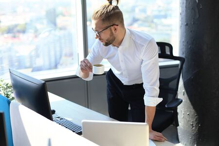 Confident young man working on laptop and drinking from coffee cup while sitting in office