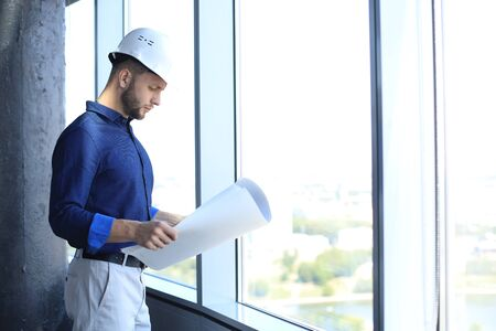 Confident young man in shirt examining blueprint while standing against a window at office