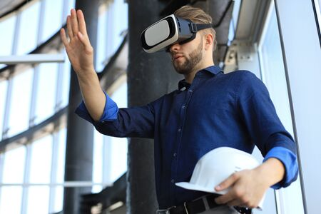 Shot of an engineer holding hardhat and wearing a VR headset in an new building. Change the way you see and experience the world Banco de Imagens