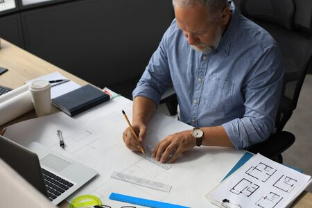 Good looking mature architect drawing something while working in the office 스톡 콘텐츠