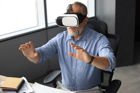 Mature businessman wearing a VR headset while sitting in modern office. Change the way you see and experience the world.
