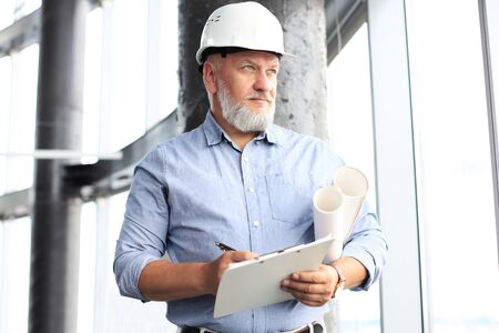 Confident mature business man in hardhat holding blueprint and looking away while standing indoors.