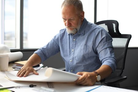 Handsome mature business man using blueprint while working in the modern working space. 스톡 콘텐츠
