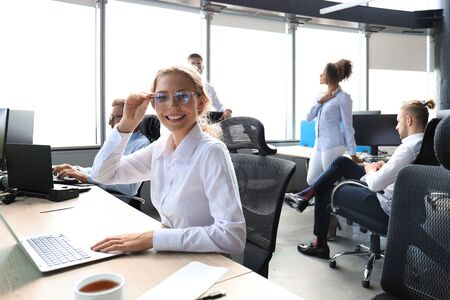 Joyful businesswoman in formalwear working on laptop in the modern office with collegues on the background 스톡 콘텐츠