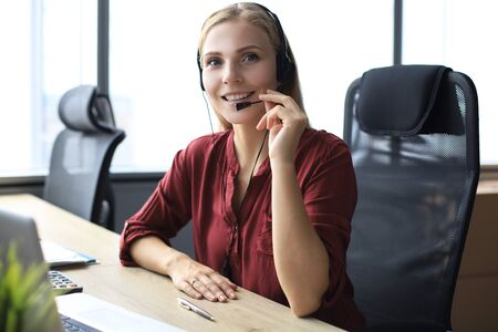 Beautiful call center worker in headphones is working at modern office