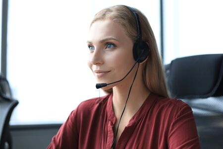 Beautiful female call center worker in headphones is working at modern office 스톡 콘텐츠