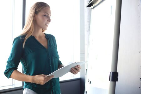Beautiful business woman is standing near flipchart and examining information at it Foto de archivo