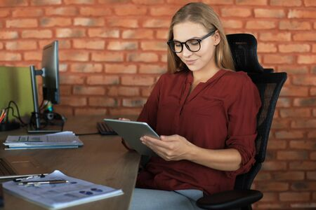 Beautiful business woman is working using digital tablet while sitting in creative office