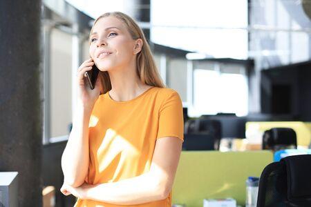 Beautiful business woman is talking on the mobile phone and smiling while standing in modern office Stock fotó