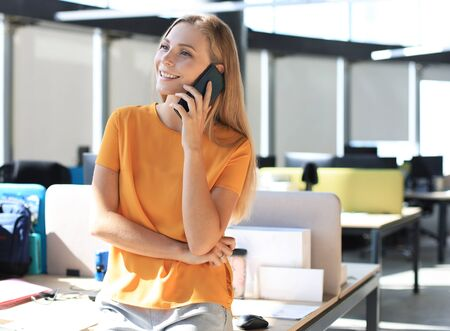 Attractive business woman talking with collegues on the mobile phone while sitting on the office desk