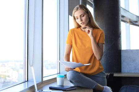 Attractive business woman holding documents and looking at them while sitting on the desk in office