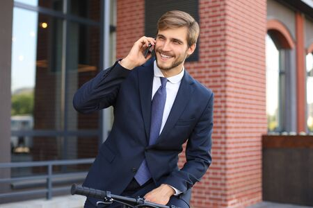 Portrait of a smiling young business man dressed in suit talking on mobile while standing with bicycle outdoors.