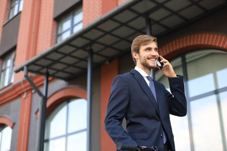 Portrait of a smiling young business man dressed in suit talking on mobile standing outdoors. Stock Photo