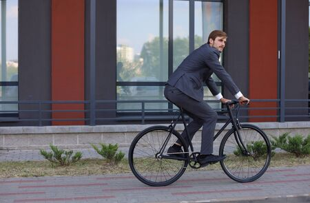 Handsome young businessman riding on his bicycle in the city. Ecologic transport concept.