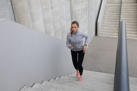 Runner athlete running on stairs. Woman fitness is jogging oudoors 写真素材