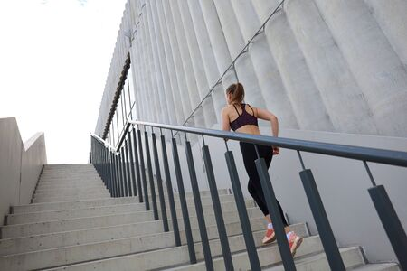 Rear view of runner athlete running on stairs. Woman fitness is jogging oudoors 写真素材