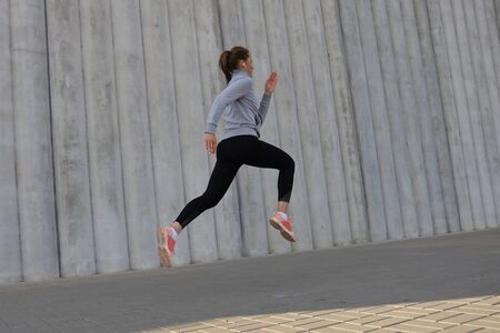 Young attractive woman with perfect slim body running outdoors. Fitness and running concept