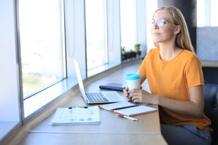 Attractive young woman is thinking about business while sitting in modern office