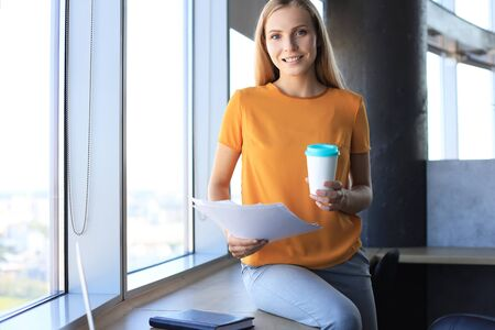 Attractive business woman is holding documents and looking at camera while sitting on the office desk Stock fotó