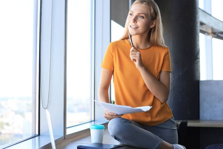 Attractive business woman is holding documents and looking away in the window while sitting on the desk in office