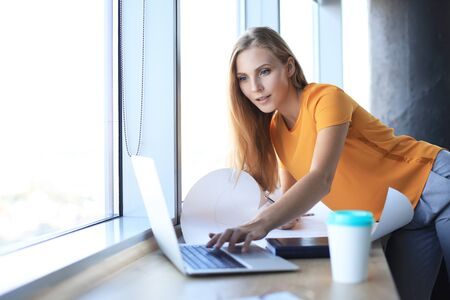 Beautiful modern woman is writing something down on the blueprint and using laptop while working in the creative office Stock fotó