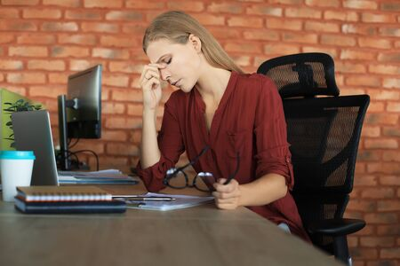 Frustrated business woman looking exhausted while sitting at her working place and carrying her glasses in hand