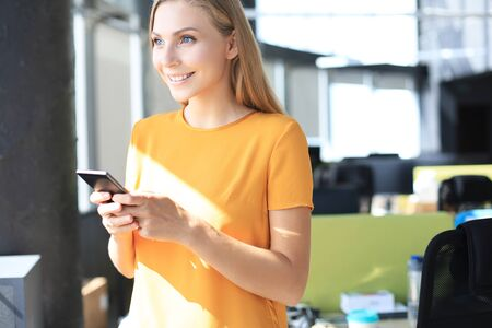 Beautiful business woman is using mobile phone while standing in the office