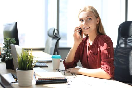 Attractive business woman talking with collegues on the mobile phone while sitting in the office desk Stock fotó
