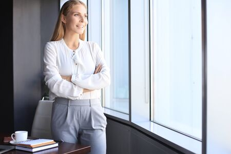 Attractive business woman looking at camera and smiling while standing in the office near the window Stock fotó