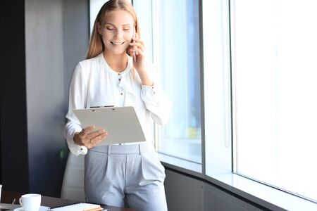 Attractive business woman talking with collegues on the mobile phone while standing near the window in the office Stock fotó