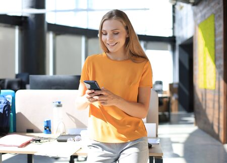 Attractive business woman is using mobile phone while sitting on the office desk