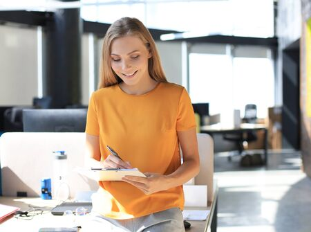 Beautiful business woman is smiling and writing something down while standing in the office