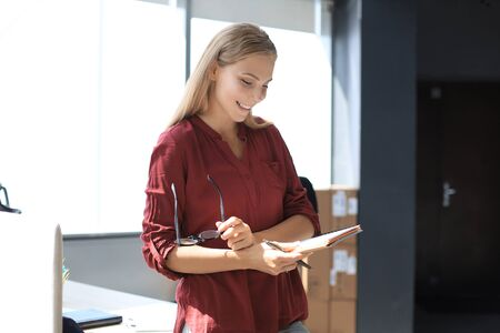 Beautiful business woman is examining documents while standing in the office