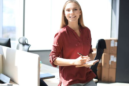 Beautiful business woman is writing something down while sitting on the office desk. Stock fotó