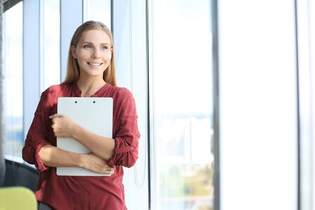 Attractive business woman looking at camera and smiling while standing in the office near the window. Stock fotó