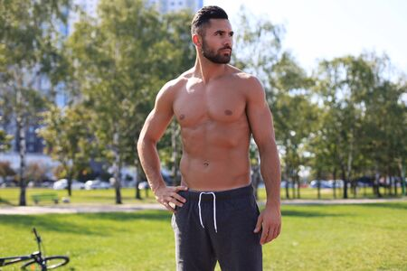 Handsome sportsman with naked torso resting while working out at sunny day in park