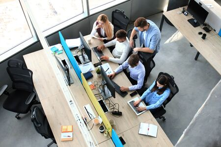 Top view of young modern colleagues in smart casual wear working together while spending time in the office.