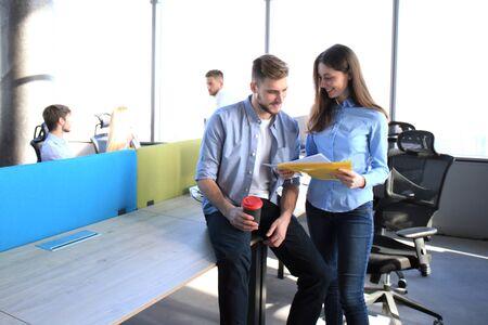 Zwei glückliche junge Leute in Freizeitkleidung lächeln und betrachten digitale Tablette während der Zusammenarbeit. Standard-Bild