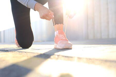 Zbliżenie kobiety sportu nie do poznania, wiązanie butów sportowych podczas wieczornego biegania na świeżym powietrzu