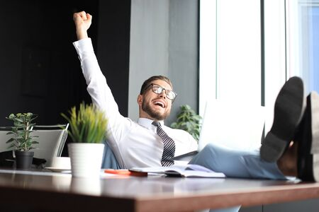 Handsome businessman sitting with legs on table and keeping arm raised and expressing joyful in office