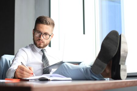 Handsome businessman sitting with legs on table and using laptop in office