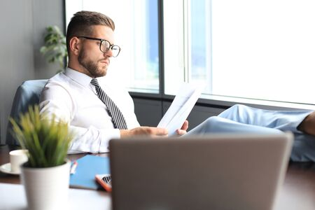 Handsome businessman sitting with legs on table and examing documents in office 版權商用圖片