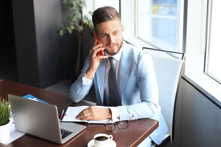 Businessman using his mobile phone in the office.