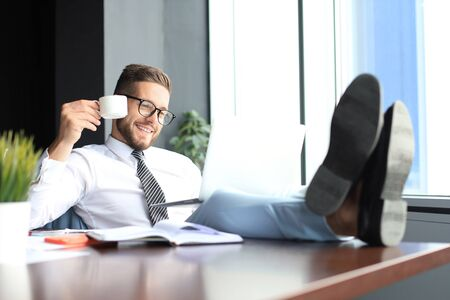 Handsome businessman sitting with legs on table and drinking coffee in office